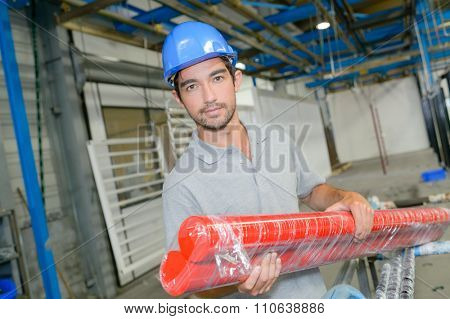 Man holding two long red tubes