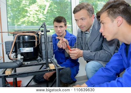 Man and students looking at an invention