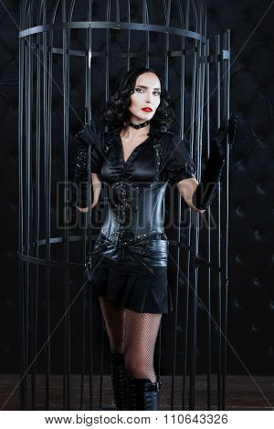 Girl In Leather Suit Is  Large Cage Dark Room.