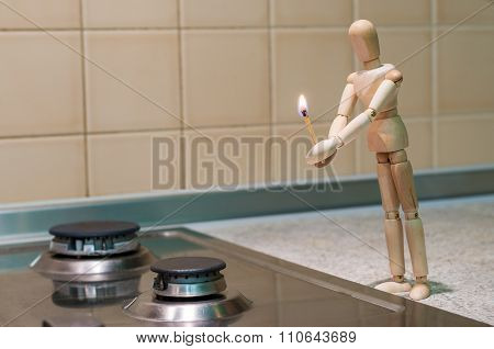 Wooden dummy, mannequin or man figurine holding a burning match and tryi to light Or ignite gas stov