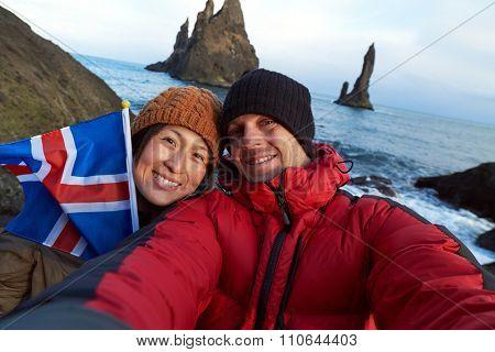Tourist couple taking selfie at black sand beach south iceland, looking at reynisdrangar basalt sea stacks, waving icelandic flag