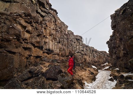 Man exploring lava rock formations in tectonic plate crack crevice in thingvellir national park iceland