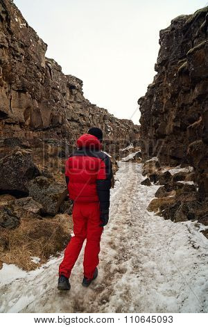 Active outdoors man walking through the crack between rocky canyon tectonic plates in Iceland