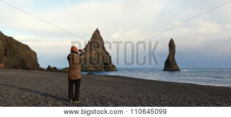 Independent traveller at black sand beach south iceland, taking photographs of reynisdrangar stone sea stacks