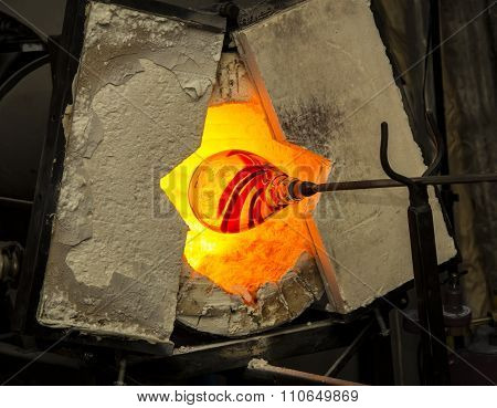 Handmade figure of melted glass, a glass blower working molten glass on a rod