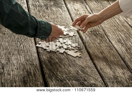 Two Hands, Male And Female, Matching Two Puzzle Pieces Over A Pile Of Other Pieces