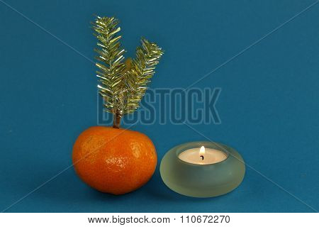 the Mandarin, tangelo,tea candle and Christmas decoration on blue background