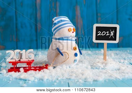 Signpost showing strikethrough year 2015 and Snowman ride red sled stand with numbers sign 2016.