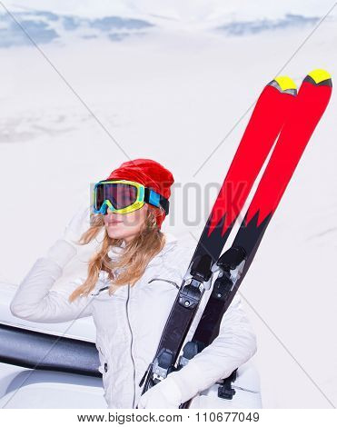 Beautiful ski instructor, sportive woman wearing mask and holding in hand ski standing in snowy mountains, active winter holidays