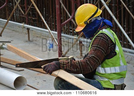Carpenter sawing timber at the construction site