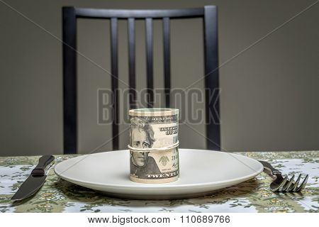 Wad of american dollars served on plate with fork and knife placed on table - business concept