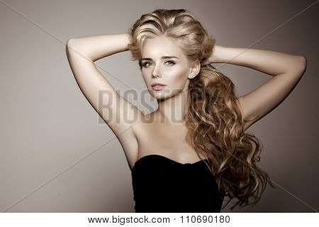 Model with blonde long hair. Waves Curls Hairstyle. Hair Salon. Updo. Fashion model with shiny hair. Woman with healthy hair girl with luxurious haircut. Hair loss Girl with hair volume. poster