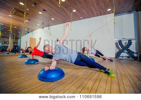 People at the health club with personal trainer, learning correct form. bosu