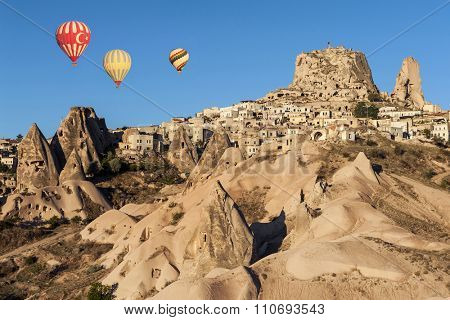Hot air balloons flying over Cappadocia near Uchisar castle at sunrise, Turkey
