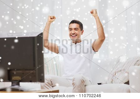 sports, happiness and people concept - smiling man watching sports on tv and supporting team at home over snow effect