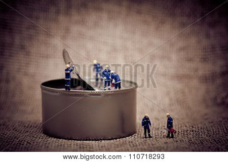 Group Of Miniature Workers Opening A Can. Color Tone Tuned Macro Photo.