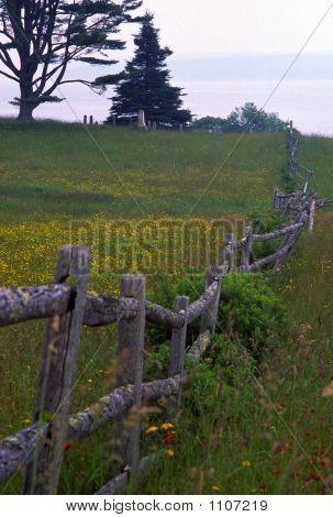 an old wooden fence runs across a meadow towards the sea near blue hill maine. poster