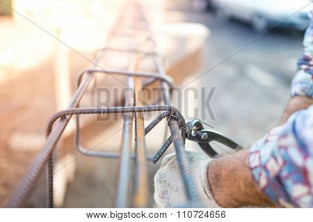 Details Of Infrastructure - Construction Worker Hands Securing Steel Bars With Wire Rod