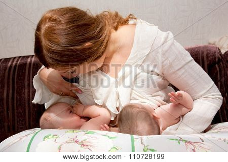 Breastfeeding twin babies with pillow device for feeding poster