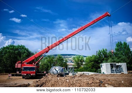 Industrial Crane Operating And Lifting An Electric Generator And concrete mobile station