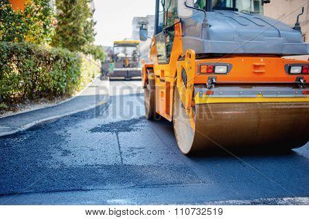 Tandem vibration roller compactor working on asphalt pavement poster