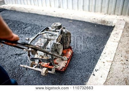 Close-up Of Asphalt Worker In Construction Site With Manual Compactor plate