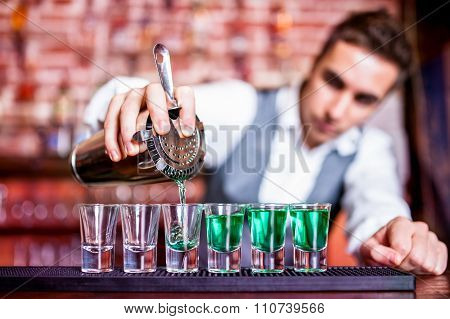 Bartender Pouring Blue Curacao Alcoholic Cocktail In Glasses On bar