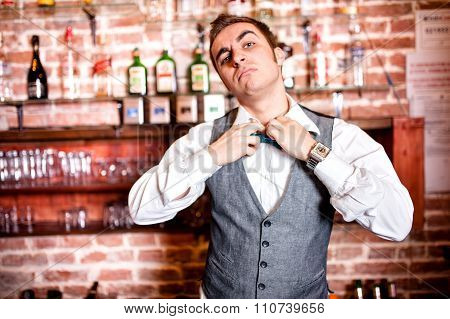 Portrait Of Angry And Stressed Barman With Bowtie Behind The Bar