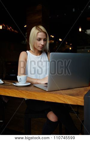 Charming hipster girl working on laptop computer during coffee break in cafe bar