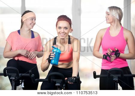 Three Women Relaxing After Cardio Exercises On Cycles
