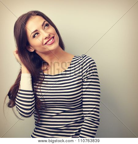 Happy Thinking Brunette Woman Scratching The Head And Looking Up