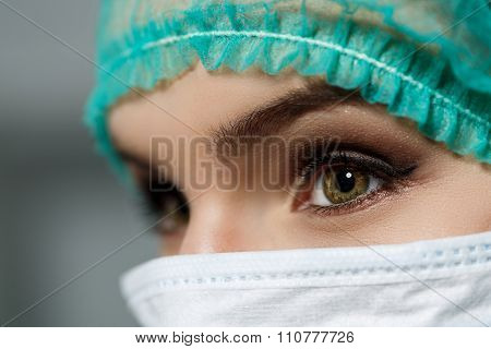 Female Doctor Face Wearing Protective Mask And Green Surgeon Cap Closeup