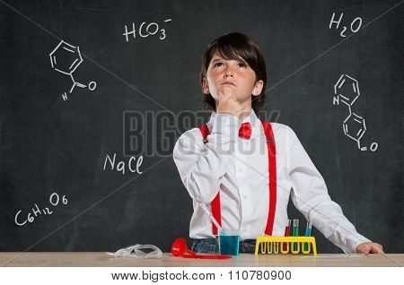 Closeup of little boy thinking while doing a chemical experiment. Pensive child thinking with liquids on desk isolated on blackboard. Little scientist looking up and thinking about new eperiments.
