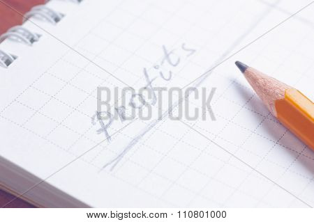 Notepad with handwritten word Profits by grey pencil lying over paper sheet cold filtered shallow de