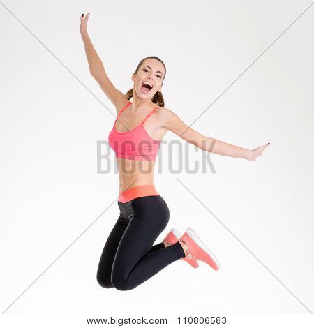 Happy joyful young fitness woman in pink top and black leggings jumping over white background