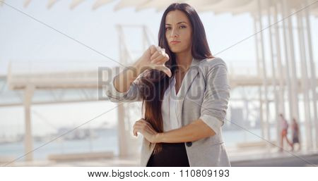 Disappointed attractive stylish young businesswoman giving a thumbs down gesture of disapproval or failure with a downcast expression