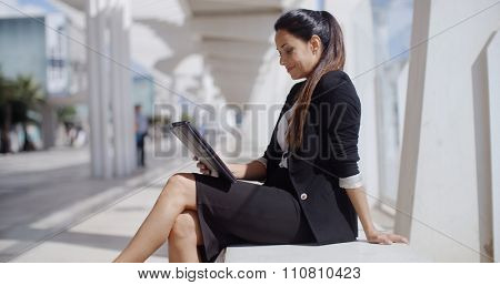 Elegant business manageress working on a laptop as she relaxes on a white bench lining a seafront promenade in a town  profile view