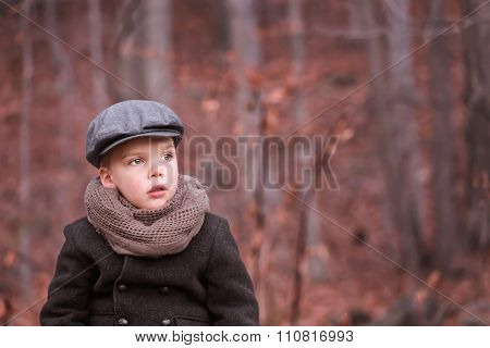 a toddler boy dressed warm looking ahead and thinking