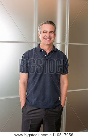 Happy casual mature business man in his office
