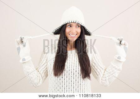 Fun hip woman holding her beanie starps