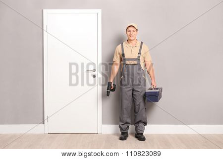 Young male locksmith holding a drill and a toolbox and standing next to a door indoors