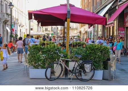 Walking People And Outdoor Cafe With Bicycle Near It On The Main Tourist Street Of Rimini, Italy