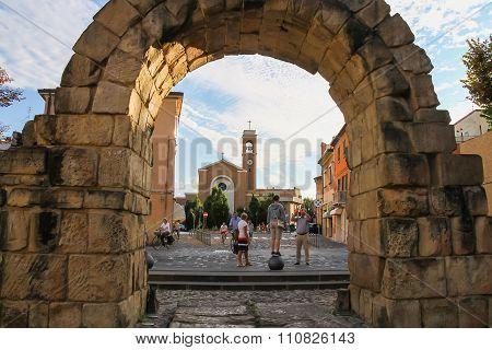 Tourists Near An Ancient Gate Porta Montanara In Rimini, Italy