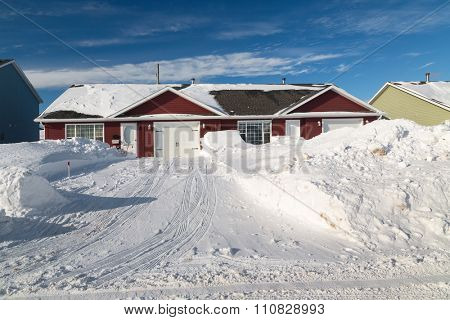 Snow piled up along a plowed road in a northern suburb.