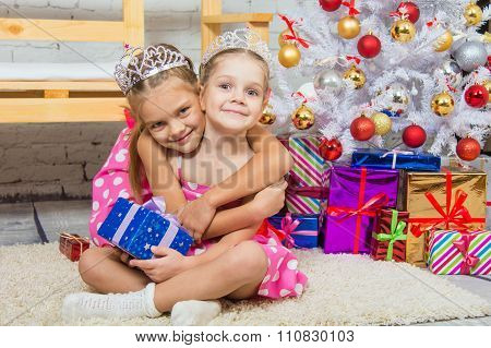 Girl Hugging Another Girl Sitting On A Mat At The Christmas Tree