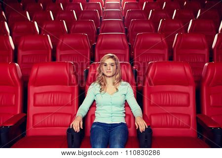 cinema, entertainment and people concept - young woman watching movie alone in empty theater auditorium