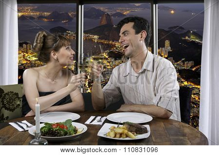 Couple in restaurant drinking wine with Rio de Janeiro in the background