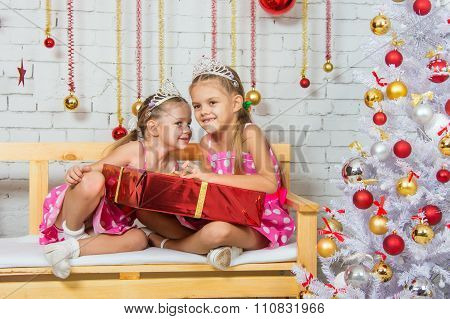 Girl Whispering A Secret That Some Other Girl Sitting On A Bench With A Christmas Present