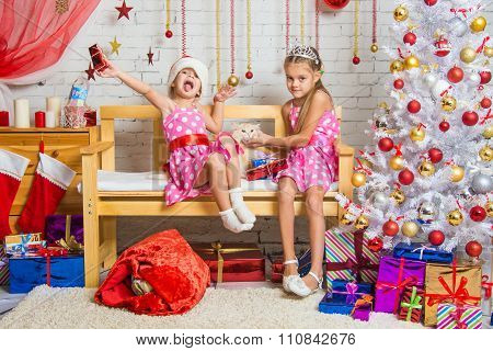 A Girl Enjoys The Present, The Other Girl Stroking A Cat In A Homelike Atmosphere Of The New Year