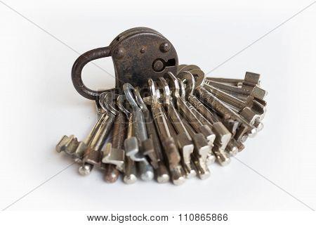 Old Black Padlock And Many Keys On White Background